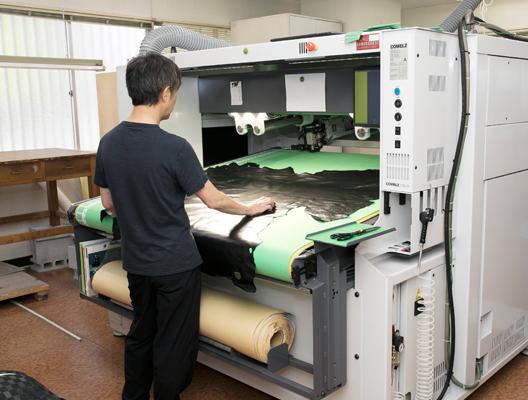 紙型にあわせて革を裁断します。<br /> サンプルの靴づくりは自動裁断機で。
